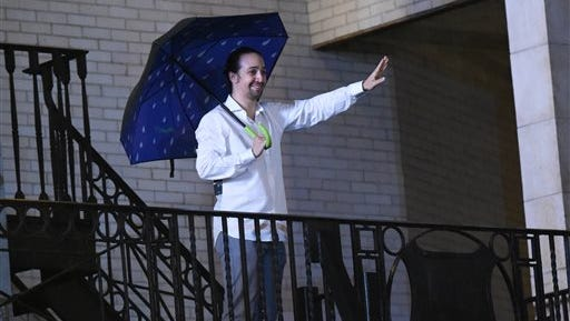 """Actor and """"Hamilton"""" creator Lin-Manuel Miranda waves to fans from atop the marquee after his final performance at the Richard Rogers Theatre on Saturday, July 9, 2016, in New York."""