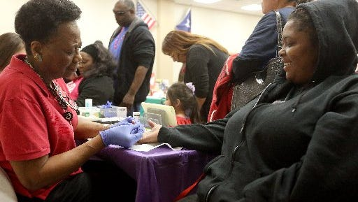 Jasmine Mosley (right) gets her glucose checked by Sally Mitchell during the Go Red for Women's Health Fair on Friday, Feb. 5, 2016, at the Corpus Christi-Nueces County Public Health District Clinic.