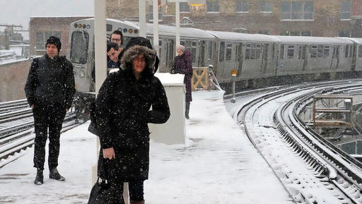Commuters wait for the train as the snow continues falling in Chicago. (AP Photo/Kiichiro Sato)