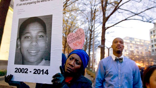 FILE - In this Dec. 1, 2014 file photo, Tomiko Shine holds up a picture of Tamir Rice during a protest in Washington. A 911 dispatcher who took a call that led to a white police officer's fatal shooting of Rice, a 12-year-old black boy who'd been playing with a pellet gun outside a Cleveland recreation center, has been suspended for eight days. Police Chief Calvin Williams stated in a disciplinary letter Constance Hollinger violated protocol.