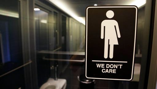 """FILE - This Thursday, May 12, 2016, file photo, shows a sign outside a restroom at 21c Museum Hotel in Durham, N.C. The Associated Press has determined that North Carolina's law limiting LGBT protections will cost the state more than $3 billion in lost business over a dozen years.That's despite Republican assurances that the """"bathroom bill"""" isn't hurting the economy."""