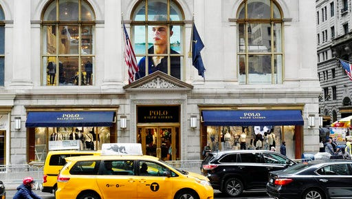 Traffic passes the Polo Ralph Lauren store on Fifth Avenue, Tuesday, April 4, 2017, in New York. Ralph Lauren Corp. said that it is shuttering the high-profile store less than three years after opening it. The closure is part of the New York fashion company's plan to save $140 million annually. The company said it will close other stores, cut jobs and shut some corporate offices, but did not provide details.