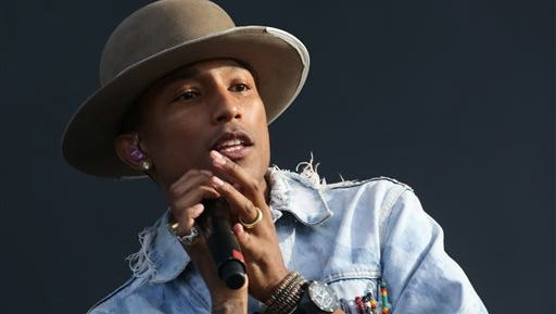 """FILE - In this July 4, 2014 file photo, Pharrell Williams performs on the main stage at Wireless festival in Finsbury Park, north London. At an event Wednesday Dec. 3, 2014 celebrating his collaboration with adidas, Williams said he remains grateful and humble about the success of his second album """"G I R L."""" (Photo by Joel Ryan/Invision/AP, File)"""