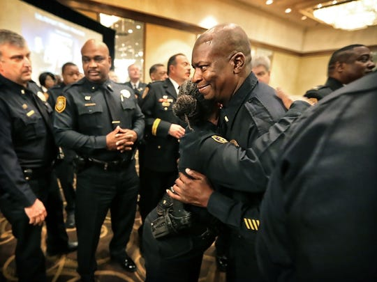 Lt. Hugh Ward (center) from Mt. Moriah Station gets a hug from fellow Lt. LaTanya Able from Tillman Station as recipients of the Memphis Police Department's supervisor of the year awards line up during MPD's annual awards ceremony at the Hilton Hotel. Awards and medals for outstanding service were handed out to 53 officers and one civilian.