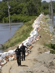 Des Moines police walk a levee near Union Park during summer flooding in 2008. Earlier that day a levee failed flooding a large portion of the Birdland neighborhood.