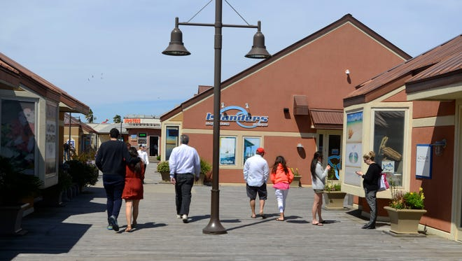 Visitors stroll the Pensacola Beach Boardwalk in this file photo.