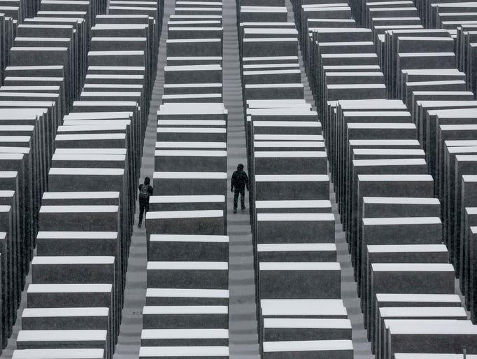 Two visitors walk inside the snow-covered Holocaust Memorial in Berlin.