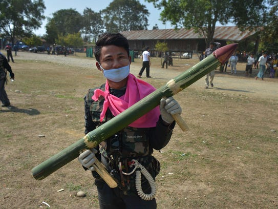 A member of Pat Jasan holds up a mock weapon made of