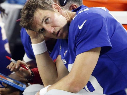 New York Giants Quarterback Eli Manning, the brother of Peyton Manning, takes a breather on the sidelines.