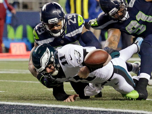 File- This Dec. 3, 2017, file photo shows Philadelphia Eagles quarterback Carson Wentz (11) fumbling the ball near the goal line and into the end zone as Seattle Seahawks' Earl Thomas (29) and Sheldon Richardson (91) move in during the second half of an NFL football game in Seattle. Many have questioned why a fumble through the end zone is treated so differently than one that goes out of bounds in the field of play. NFL senior vice president of officiating Al Riveron said earlier in the year that the idea of a rule change has been brought before by the competition committee and he expects it will be discussed again. But for now, it remains a turnover even if it might not seem logical. (AP Photo/John Froschauer, File)