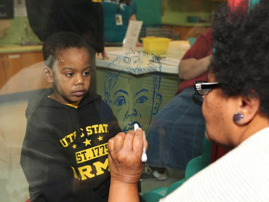 Local artist Mary Watkins draws a portrait of a child who visited Discovery Center at a previous Martin Luther King Jr. Day event.