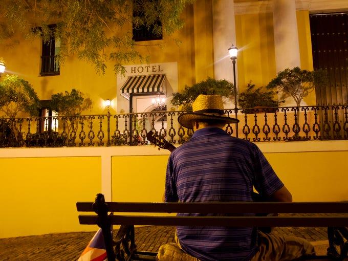 A street performer sings folk songs and plays guitar