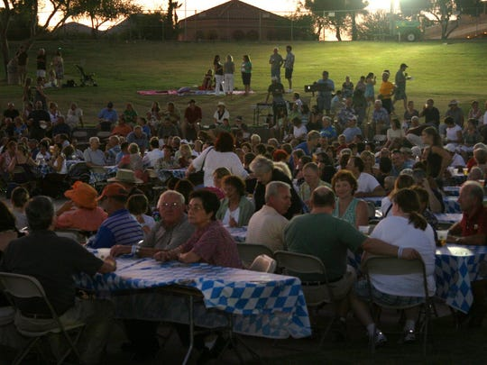 People gather at tables in center of the festival at the Fountain Hills Oktoberfest at Fountain Park.