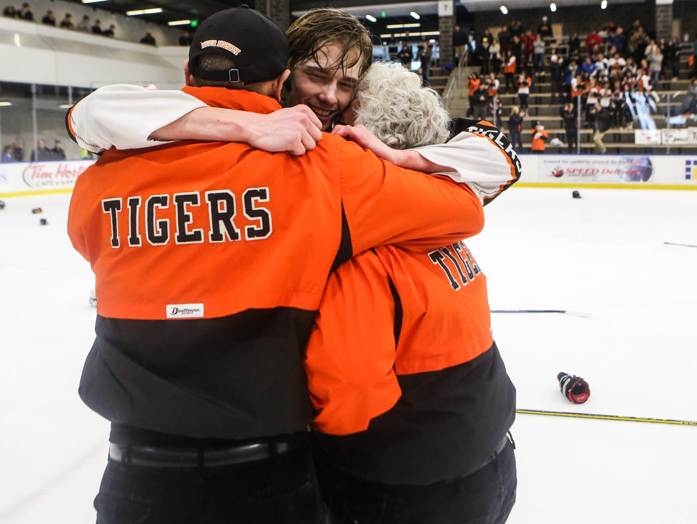 Mamaroneck's Alex Ewald (center) hugs Head Coach Michael Chiapparelli (right) and Assistant coach Art Bruno after winning the game. Mamaroneck defeated West Genesee 1-0 and won the NYSPHSAA Division 1 HarborCenter in Buffalo, NY.