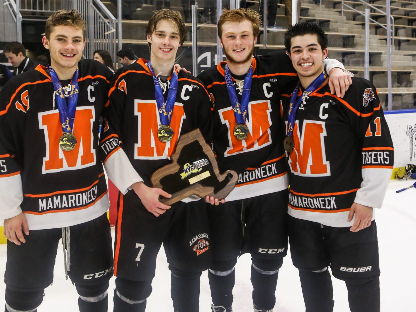 Mamaroneck's Will Kirk (19), Alex Ewald (7), Chris Conley (22), Will Arbo (11) take a group photograph with the state plaque after winning the game. Mamaroneck defeated West Genesee 1-0 and won the NYSPHSAA Division 1 HarborCenter in Buffalo, NY. Nick Serrata - For The Journal News