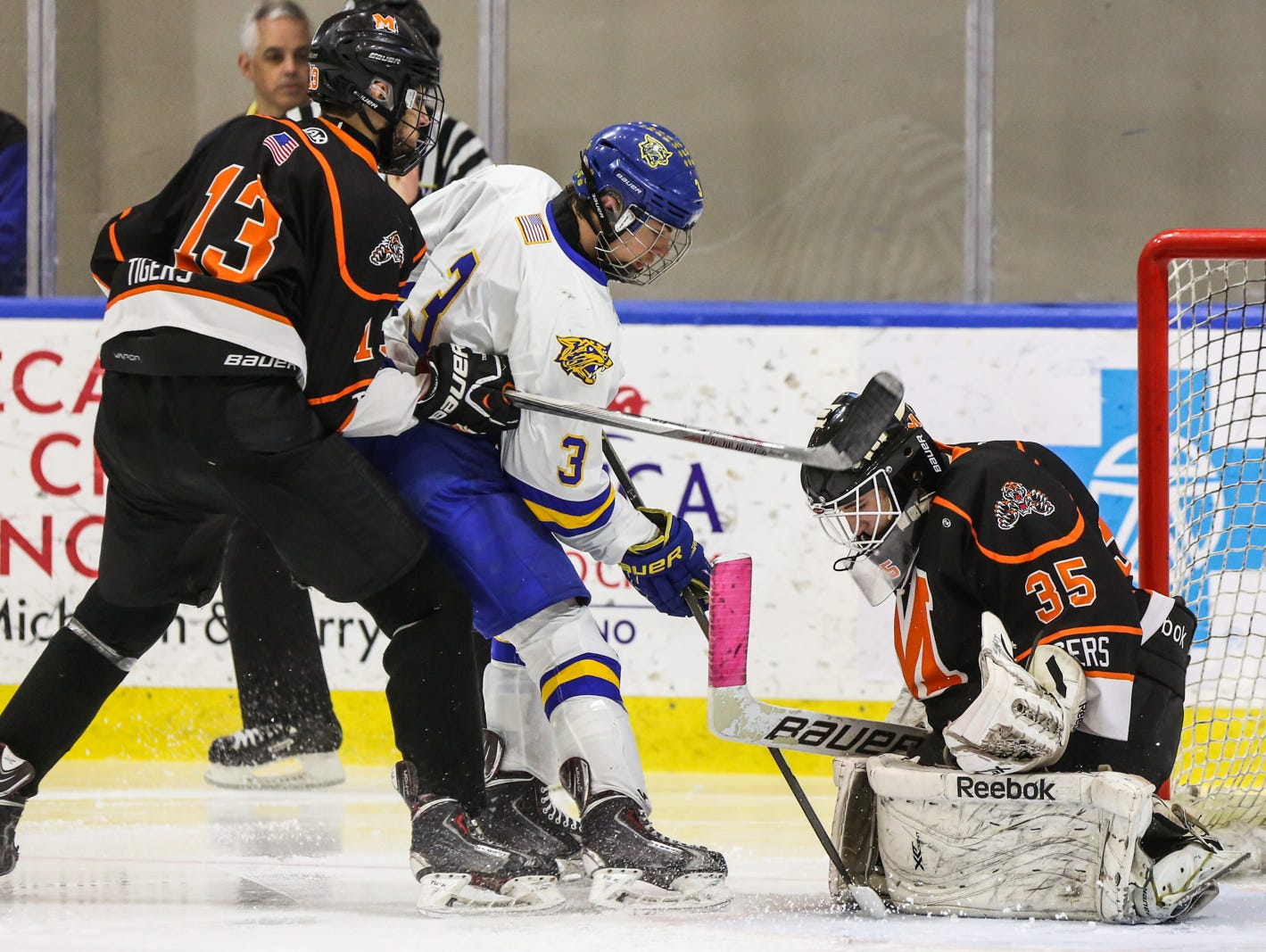 Mamaroneck goalie Tommy Spero makes a save agaisnt West Genesee's Jay Considine as Kesin Ryan Dehejia checks him in the second period of Sunday's Division 1 state championship game in Buffalo. Mamaroneck defeated West Genesee 1-0.