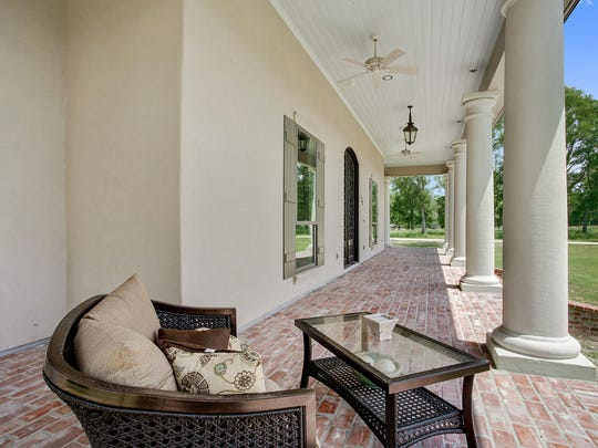 The front porch features gorgeous columns and brick walkways.