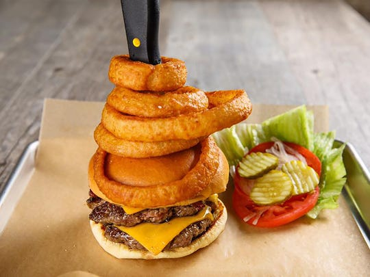 Jimmy P's Man vs. Burger features two 5-ounce Wagyu beef patties, bacon, cheddar, Charred steak sauce and a beer-battered onion ring stack.