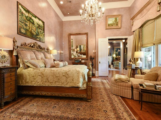 The luxurious master suite has beautiful wall treatments and custom lighting.