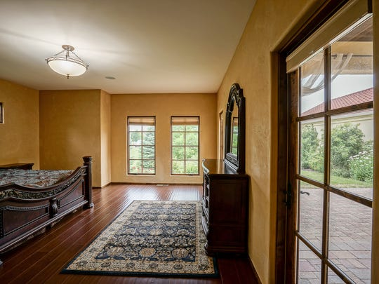 The master bedroom is located on the main floor and includes access to the backyard.