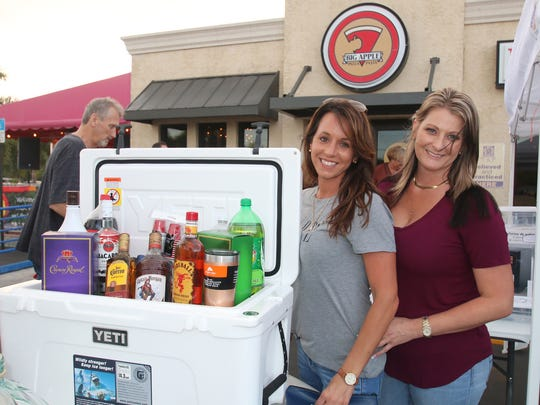 """Megan Nuccio, left, and Sara McKinney with a raffle item at the """"sLiver of Hope"""" fundraiser at Big Apple Pizza on Feb. 21."""