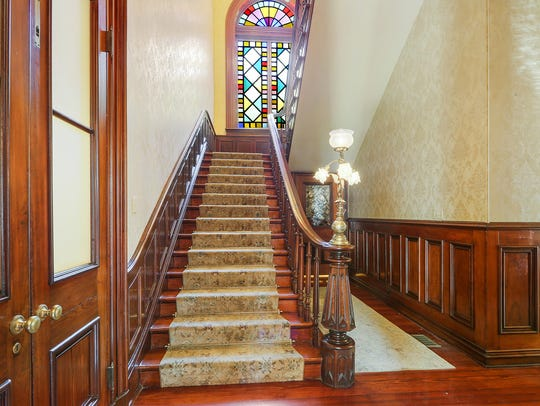 A grand staircase graces the home's entry.