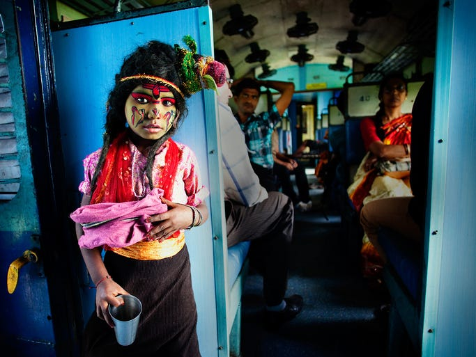 """A photograph titled """"Poor God"""" was one of 10 winners in the open competition of the 2014 Sony World Photography contest. The image, which was the top shot in the people category, shows a young child dressed as the Hindu god Lord Shiva on a train during the traditional Durga Puja Festival in India."""
