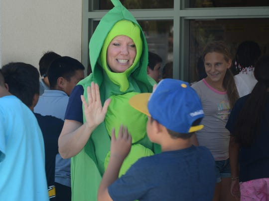 Marta Sand, nutrition services site manager for DSUSD, greets students with a high-five as they enter the lunch line.