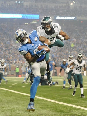 Calvin Johnson hauls in his second TD catch, in the third quarter, despite the efforts of flying Eagle Eric Rowe.