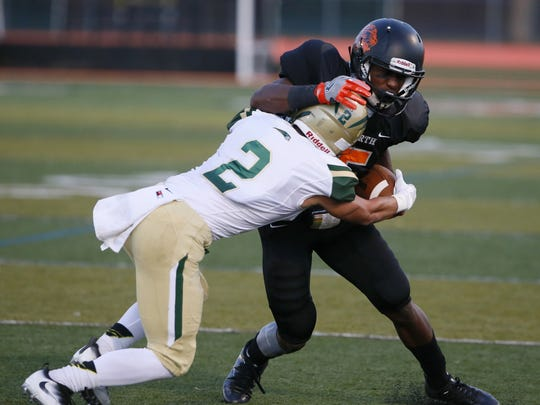 Logan Whelan (left) of Red Bank Catholic tackles Dwight Wilkerson  of Middletown North during high school football game at Middletown North on  Sept. 17, 2016.