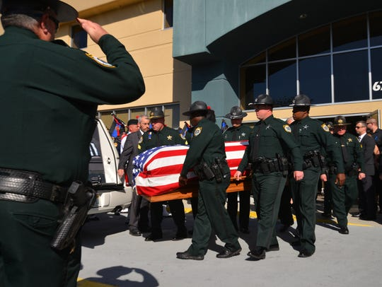 The Honor Guard carries out the flag draped casket.