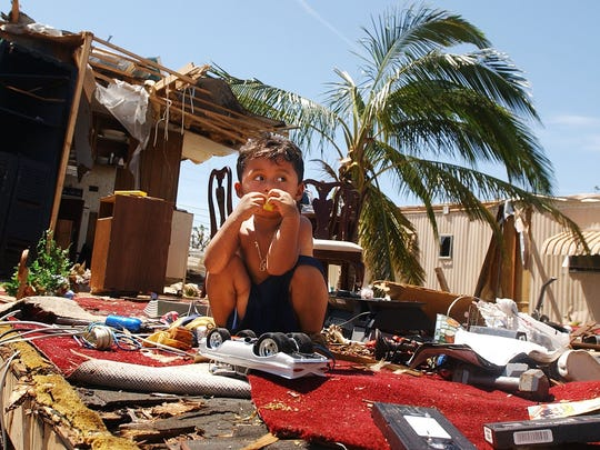 Jorge Vergara, then 3, plays in the wreckage of his grandparents' destroyed mobile home at the Pink Citrus Mobile Home Park in 2004.