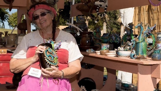 """Stacy Schwarz of Gila, N.M., sets up her exhibit of  """"functional animal sculptures"""" at the recent  Doña Ana Arts Council Renaissance ArtsFaire in Young Park."""