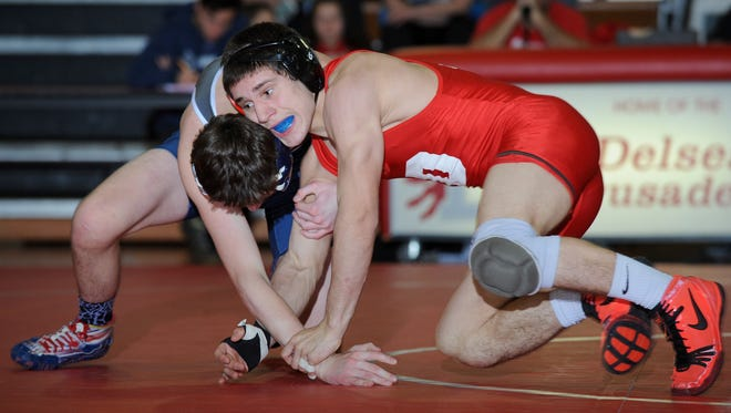 Delsea's Tim Spatola, right, grapples with St. Augustine's Robert Woodcock at 132 pounds on Saturday. The two freshmen have had to learn fast at their powerhouse programs.