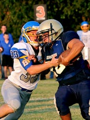 Notre Dame's Devyn Quintero (right) battles for yardage