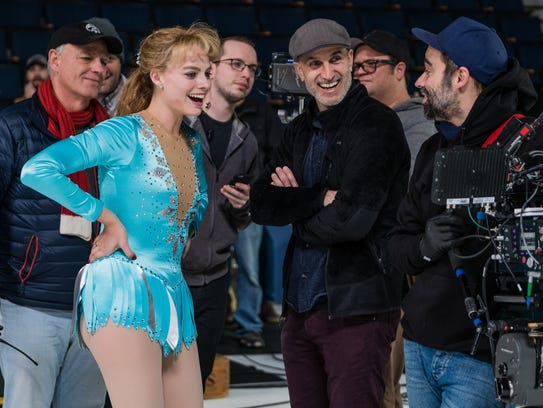 Wearing her figure-skating garb, Margot Robbie watches