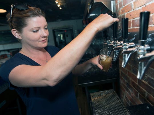 Co-owner Candice McMath pours beer from the tap on