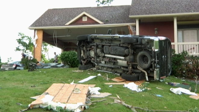 In this still frame from video provided by WQOW, a vehicle is seen on the lawn of a home near Martell, Wis., in Pierce County on Thursday, June 29, 2017, after a tornado touched down in western Wisconsin on Wednesday.