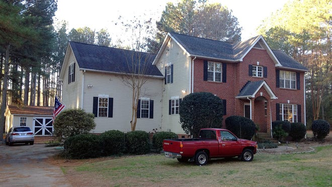 Cars are parked at a home in York, S.C., on Tuesday, Jan. 16, 2018, where multiple deputies responding to a domestic violence call were shot and wounded. State Law Enforcement Division spokesman Thom Berry said Christian Thomas McCall is the man officers think shot and wounded the officers early Tuesday.