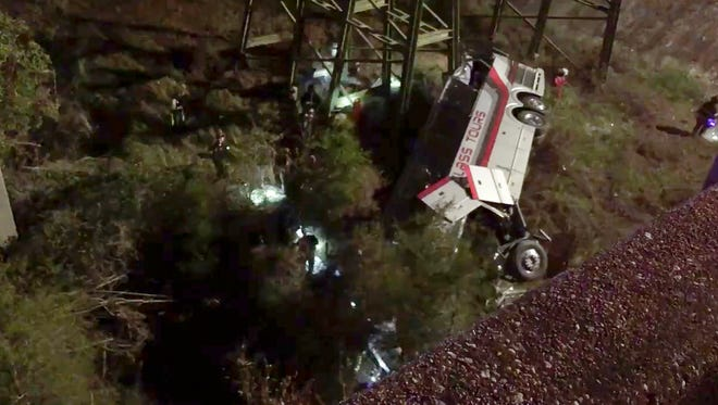 This photo provided by Jesus Tejada shows first responders searching around a bus that plunged into a ravine, Tuesday, March 13, 2018, on Interstate 10 in Loxley, Ala.  Several people were on board, and all of them were brought to 10 hospitals in Alabama and Florida, either by helicopter or ambulance, said Baldwin County (Ala.) Sheriff Huey Hoss Mack.  ( via AP) ORG XMIT: NY107