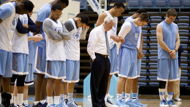 North Carolina head coach Roy Williams, center, and his players observe a moment of silence in honor of former North Carolina head coach Dean Smith, during a basketball clinic for Special Olympics athletes, Sunday, Feb, 8, 2015, in Chapell Hill, N.C.