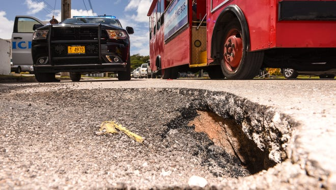 Police block off an outer lane of Aspinall Avenue in Hagåtña after holes formed on its surface on Thursday, Feb. 8, 2018. Department of Public Works patched up the break in the pavement, which was possibly linked to underground work performed by Guam Waterworks Authority.