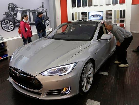 Tesla representative John Van Cleave, right, shows