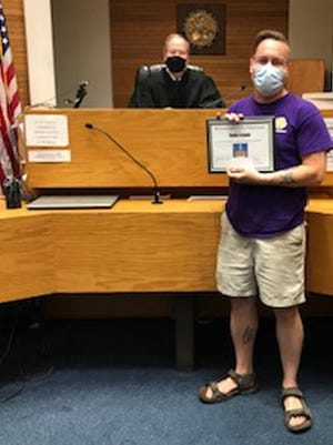 Program participant Daniel Zeigler (foreground).holds the drug court graduation certificate presented to him by Judge William E. Poncin, background. He was among three program participants who graduated Drug Court on Thursday.