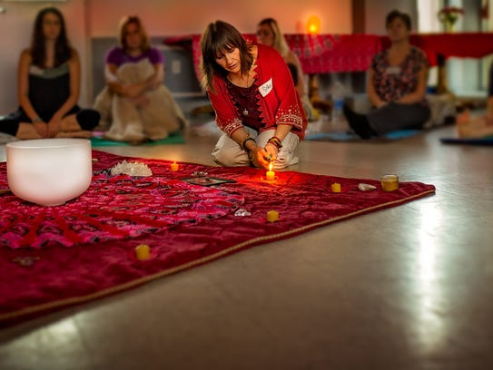 Silke Tyler lights a candle during one of her holistic