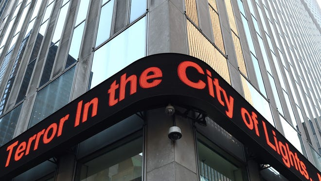 "The headline ""Terror in the City of Lights"" flashes on the News Corp. Building on 6th Avenue in New York  on Nov. 14, 2015,  the morning after the terror attacks in Paris."