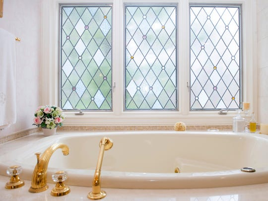 Leaded and beveled glass over the Roman tub has colored