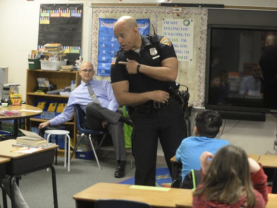 Officer Tim Davis talks about his uniform as he and