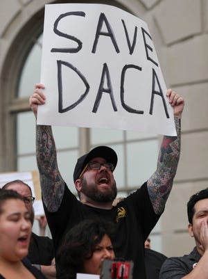 Paul with Louisville Socialist cheers during a DACA protest organized outside of the Federal Building in downtown Louisville on Tuesday. Sept. 5, 2017