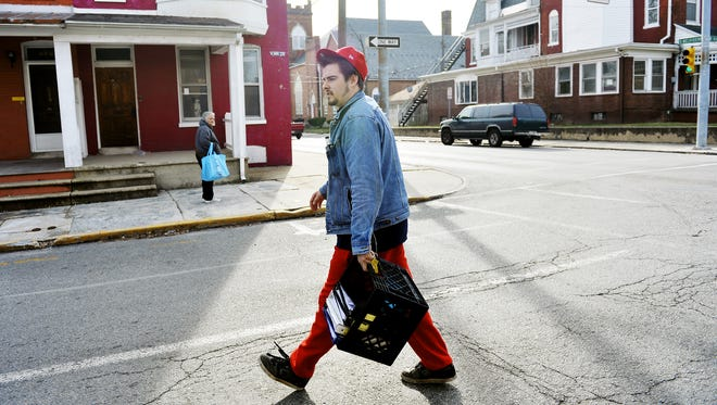 """Tanner Doyle, 24, crosses West King Street to prepare an Abundant Life Outreach van for his food deliveries. Doyle, who lives in True North recovery house, operated by the same church that houses Abundant Life, said he relapsed three times since coming to True North in June 2015 but feels confident in his ability to stay clean after a family intervention in November. """"I've never felt happier in my life,"""" Doyle said. """"I've never felt as accepted in my life. I feel no need to use drugs."""" True North is one of about 80 recovery homes in York that house people who are trying to trying to get and stay sober."""